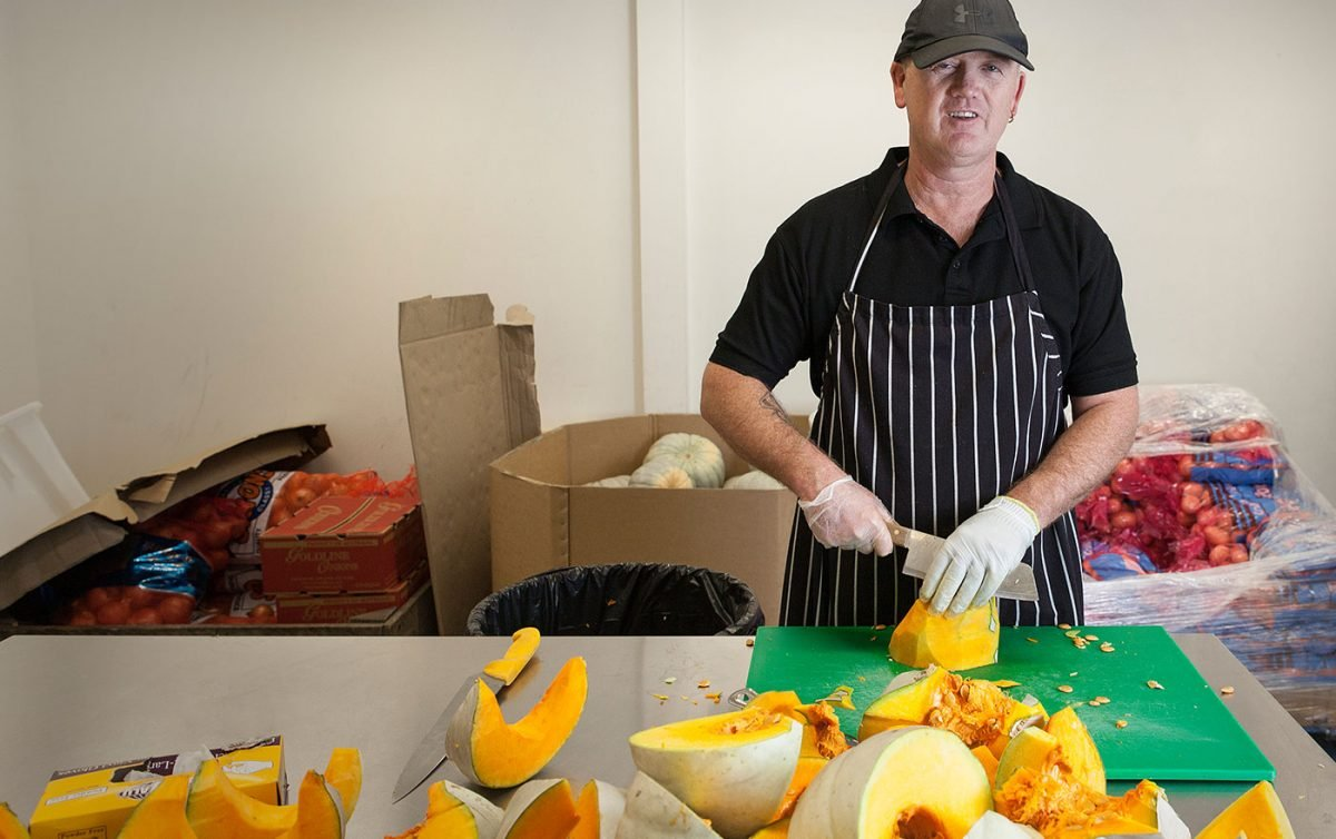 Man smiles whilst cutting up pumpkin in commercial kitchen
