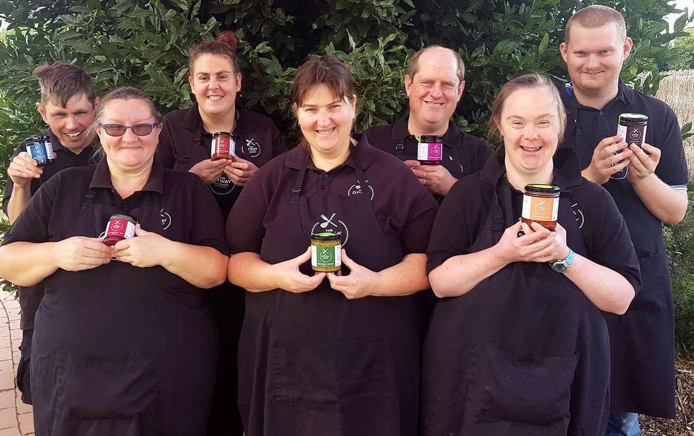 Otway Kitchen workers smile holding product