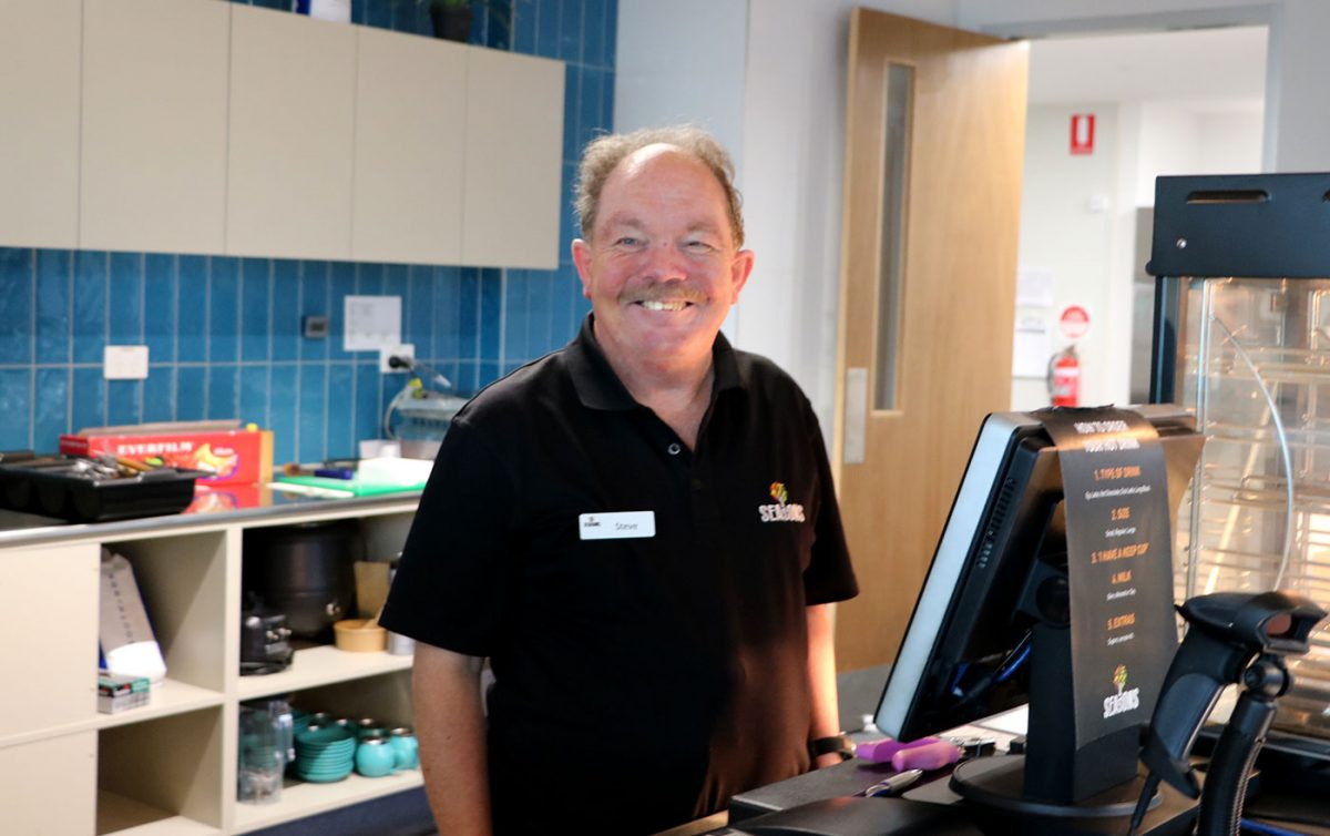 Man smiles working behind food service counter at Seasons Cafe