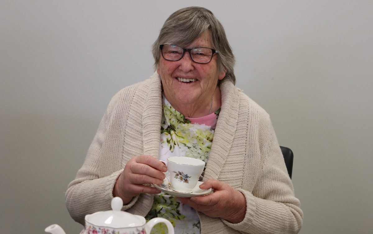 Aged care woman smiling whilst enjoying some tea