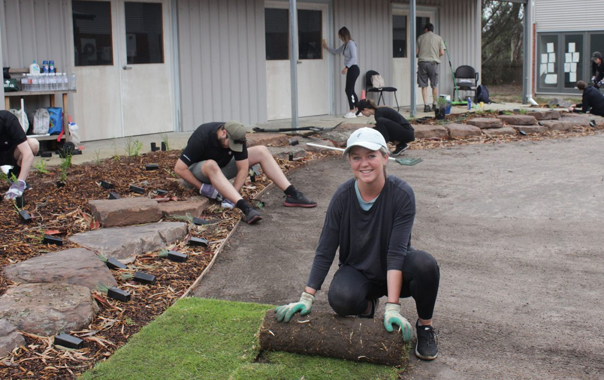 Woman smiling for photo as she rolls out turf at Gen U working bee