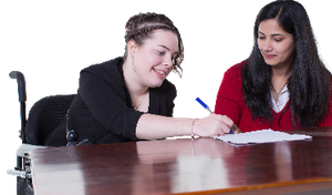 A person filling out some paperwork with a support worker