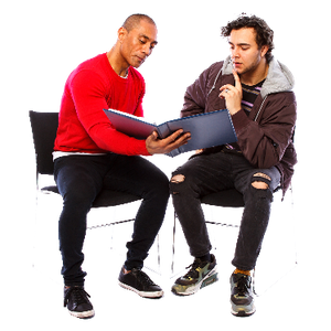 Two men sitting down reading a booklet together