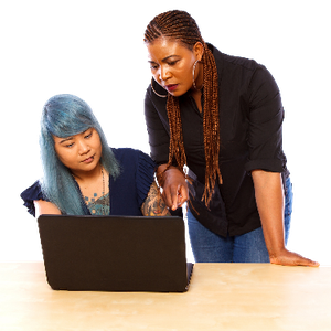 A woman sitting down using a laptop. A support worker leans over helping.