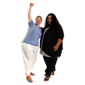Two people. One woman is holding her arm up to celebrate. The other woman is standing close to support her.