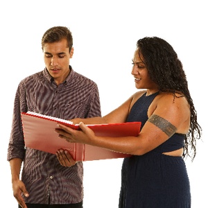 A woman pointing and explaining a booklet to a man