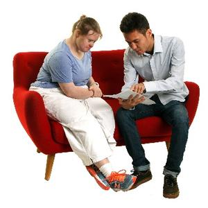 Two people sitting on a couch. A support worker is explaining paperwork to another person.