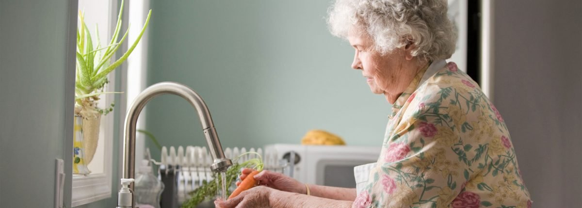 elderly woman washing carrot in floral shirt