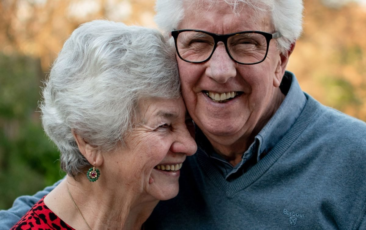 Aged care couple hugging and smiling