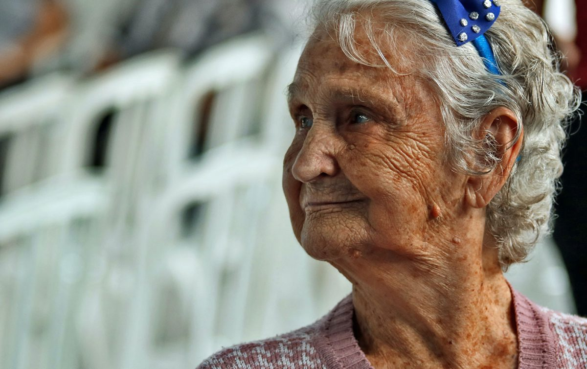 Aged care woman looking away from camera smiling