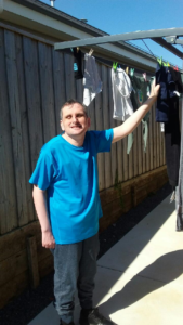 Man stands smiling next to clothes line