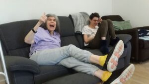 Two women smiling sitting on couch